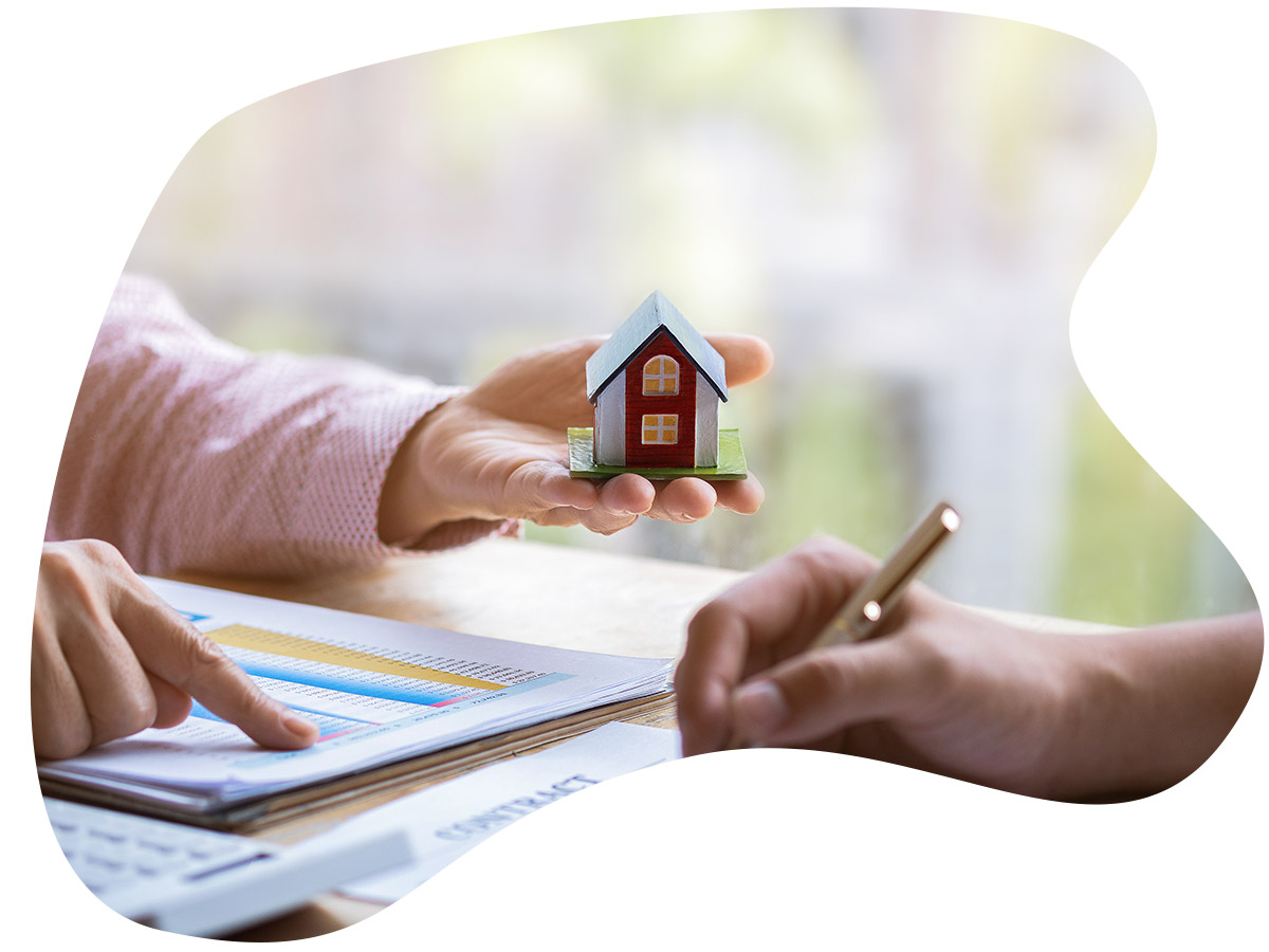 Real estate agent pointing finger on document showing total cost while holding a small home.